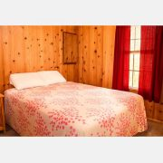 The comfortable bed inside a cozy cedar cabin