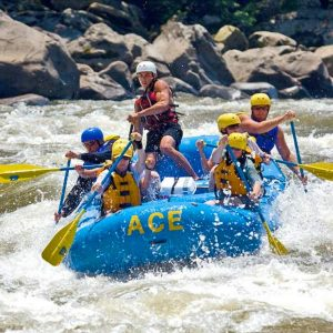 a group paddles through the whitewater rapids of the lower new river