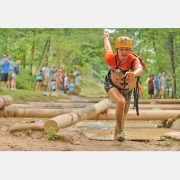 A woman racing out of the mud obstacle course