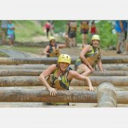 Women climbing over logs of the mud obstacle course