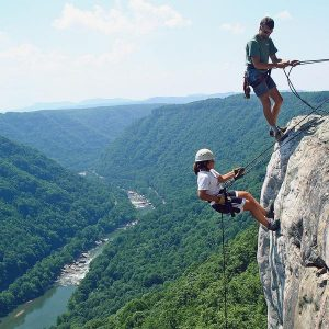 A woman and man begin their rappel on the new river gorge