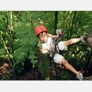 A young boy smiles as he rappels over a cliff at ACE Adventure Resort