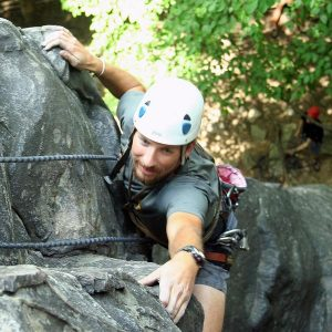 A climber pulls himself up a cliff on the New River Gorge