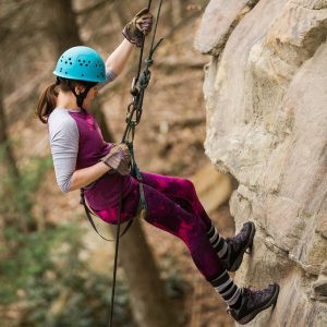 A female climber rappels at ACE Adventure Resort