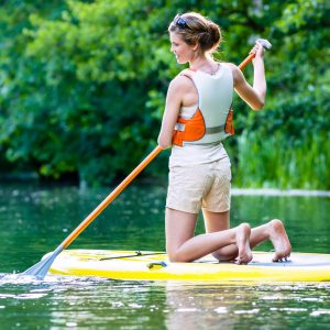 young lady kneeling on paddle board