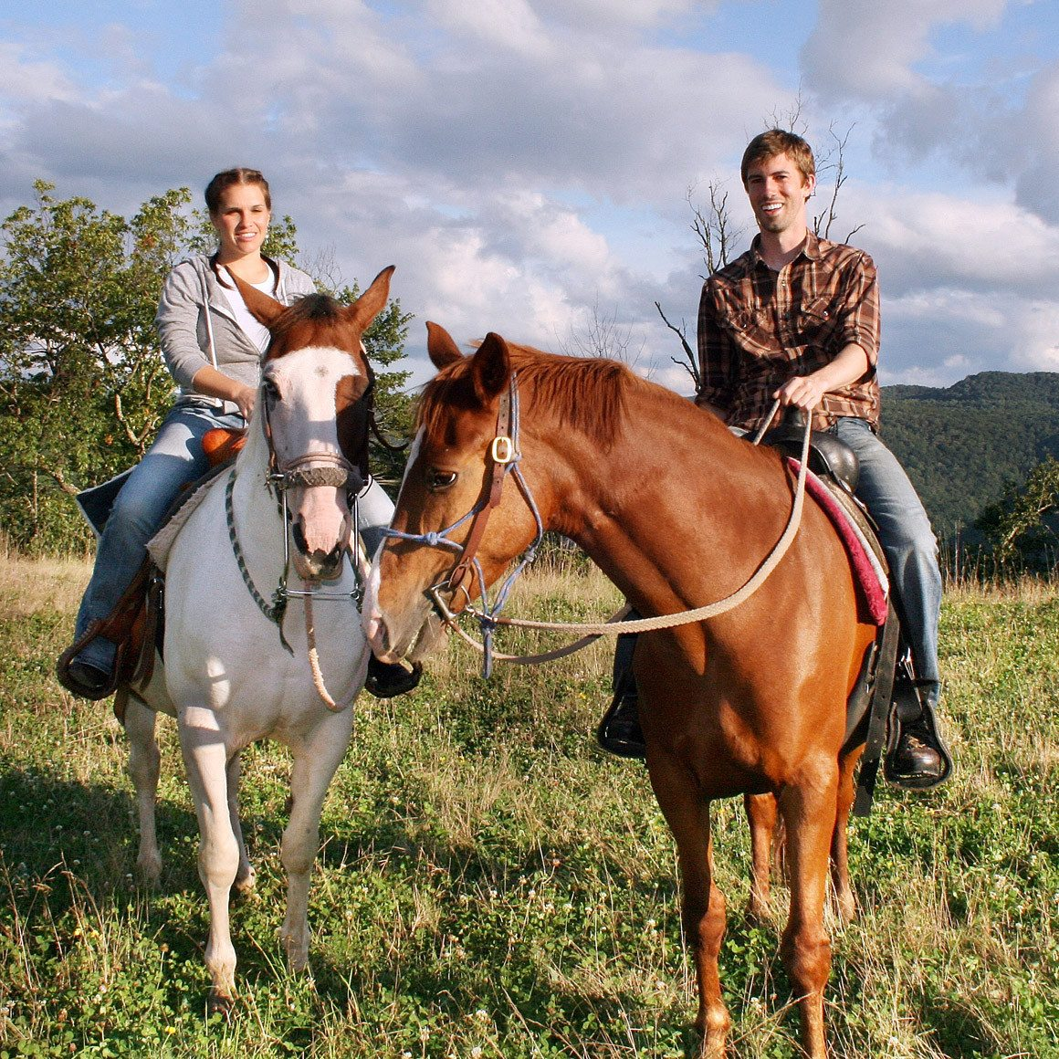 a young couple enjoying a sunset horseback ride