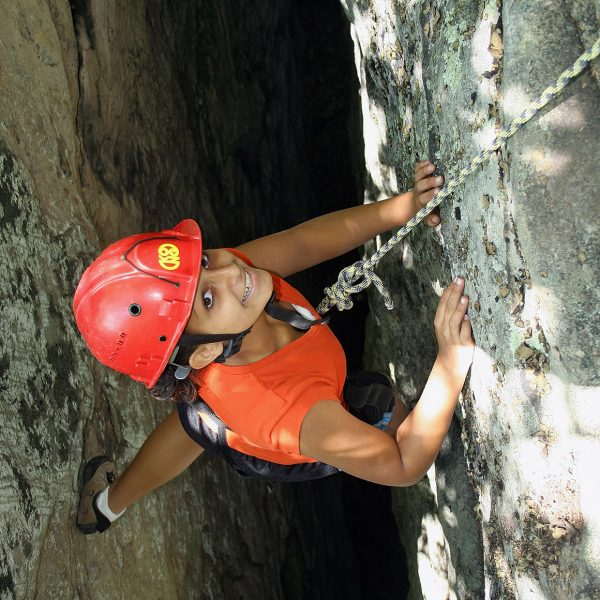 A young girl climbing through a crack of the upper gorge
