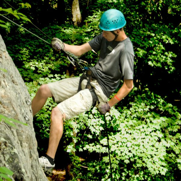 A male climber rappelling a steep cliff at ACE Adventure Resort