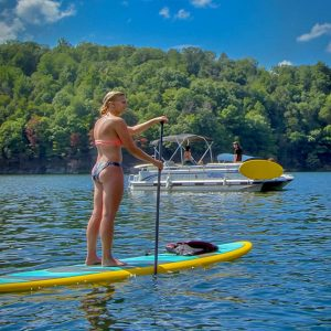 A woman stand up paddleboards across the beautiful summersville lake