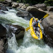 A man in a duckie rides over a waterfall during Summer Gauley