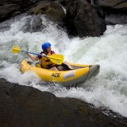 A woman paddling a duckie in some wild white water on the summer gauley