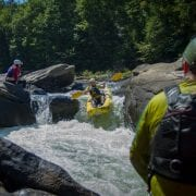 A man in a duckie rides over a waterfall during Summer Gauley while his companions cheer him on