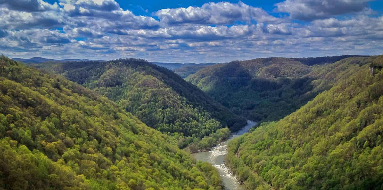 Scenic photo of a sunny horizon with fluffly clouds over the new river gorge national recreation area