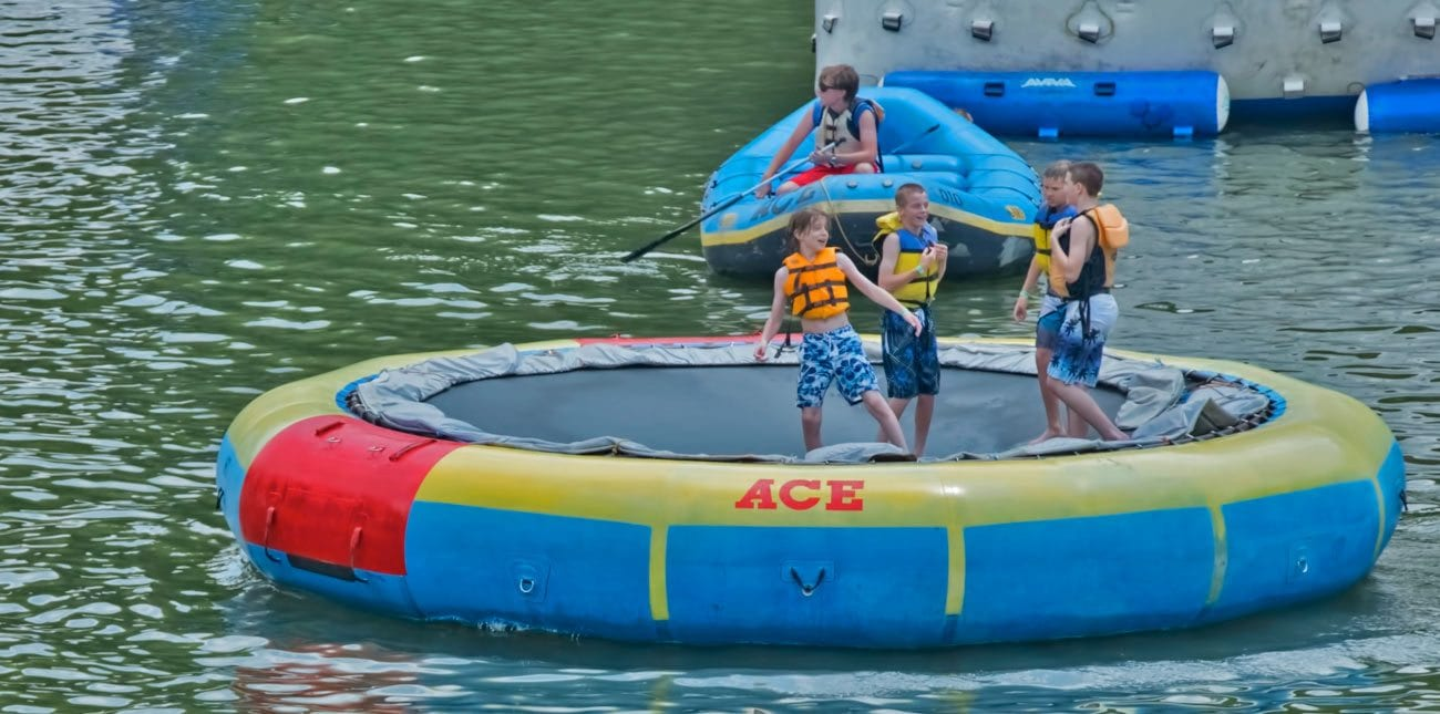 Kids jump on an innertube trampoline on ace adventure resort lake at the wonderland waterpark
