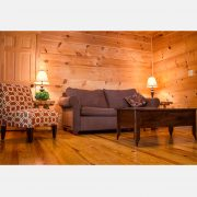 A comfy couch and chair by a oak coffee table in the black bear cabin