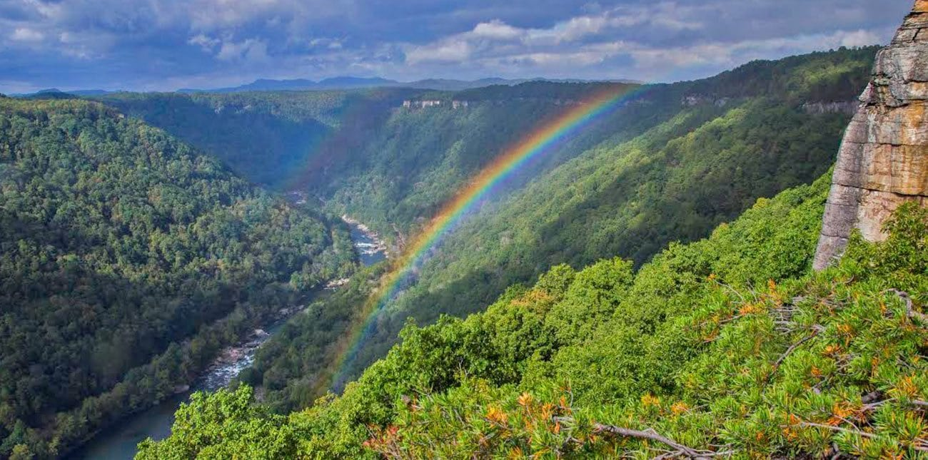 A rainbow shines over the new river gorge on a sunny day after rain in fayette county west virginia