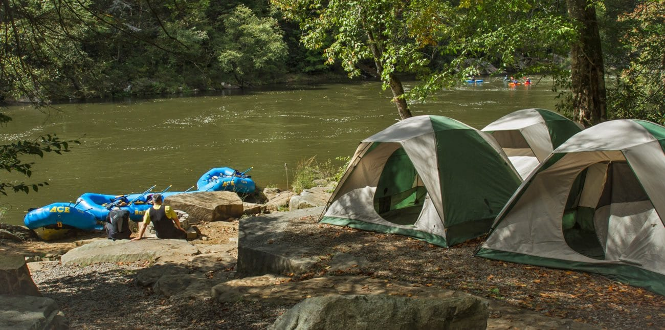 An overnight camp site with tents and whitewater rafts set up next to the gauley river in west virginia
