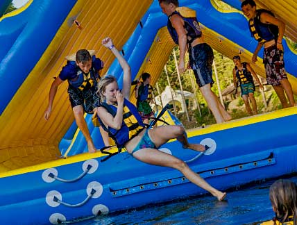 girl holding her nose while jumping from inflatable at the waterpark