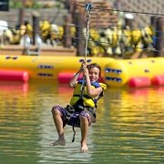 A boy smiles as he ziplines towards the water at Wonderland Waterpark