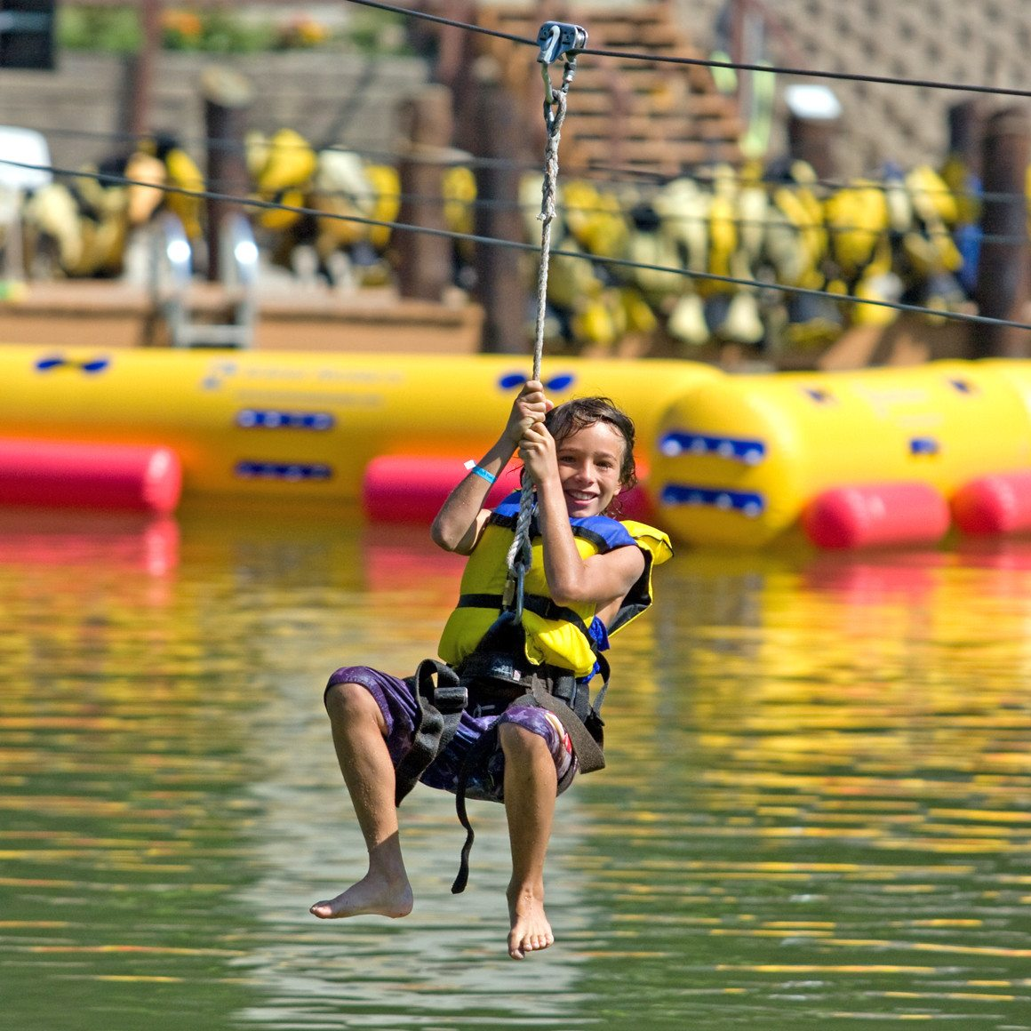 A boy smiles as he ziplines towards the water at Wonderland Waterpark