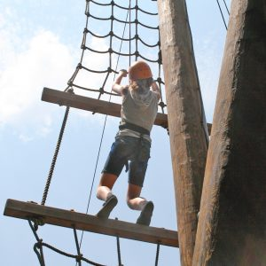 A girl climbs the challenge course at ACE Adventure Resort
