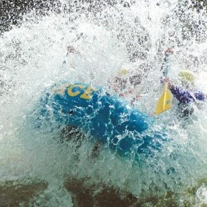 A group splashing through a rapid on an extreme gauley river rafting adventure