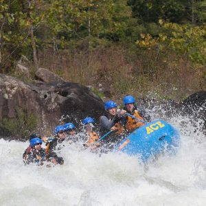 A group splashing over rapids on an extreme gauley river rafting adventure