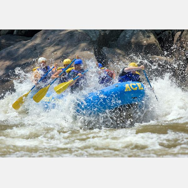 5 people in a raft paddling through extreme white water on the Lower New River