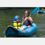 A woman and boy riding an inflatable duckie on the upper new river