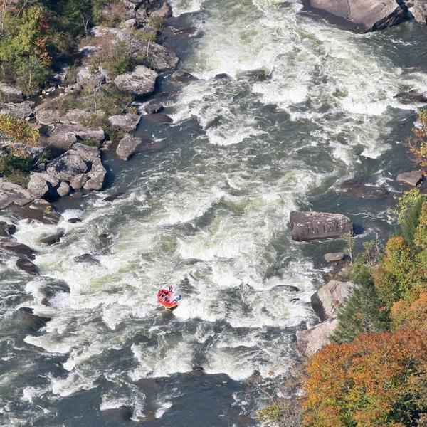 Aerial view of a raft riding through the gauley river rapids