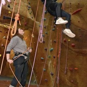 a climber rappelling from the climbing wall at inside out climb and mini golf