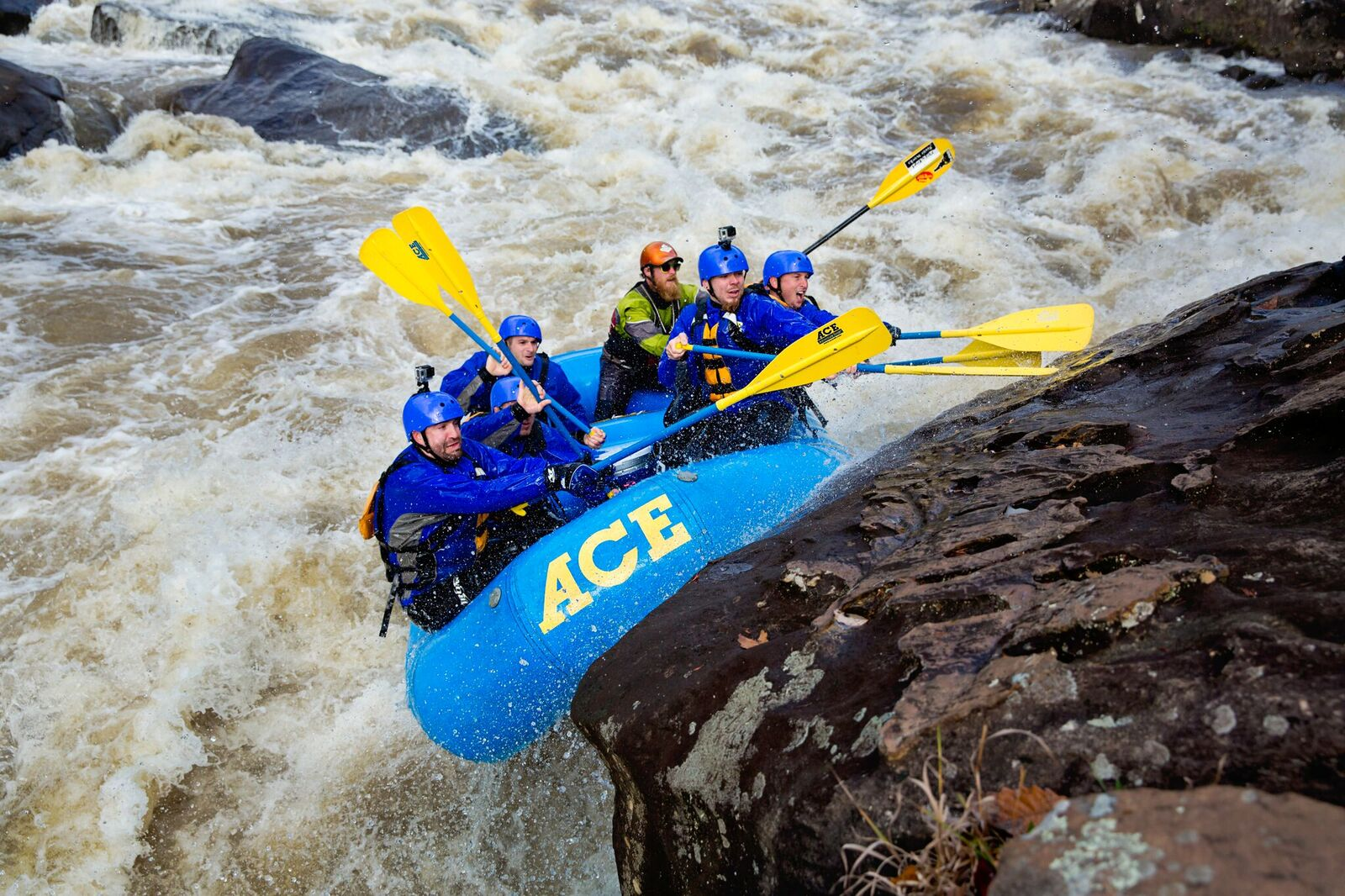 A group of 6 extreme adventurers reach for pillow rock on the Upper Gauley River