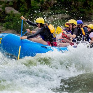 A white water rafting group splashing through the rapids of the Lower New River