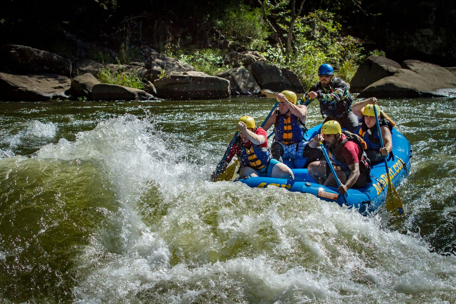 A group of 5 paddling into the rapids