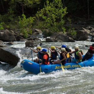 A group of 6 adventurers are guided along the hard flowing rapids of fall gauley