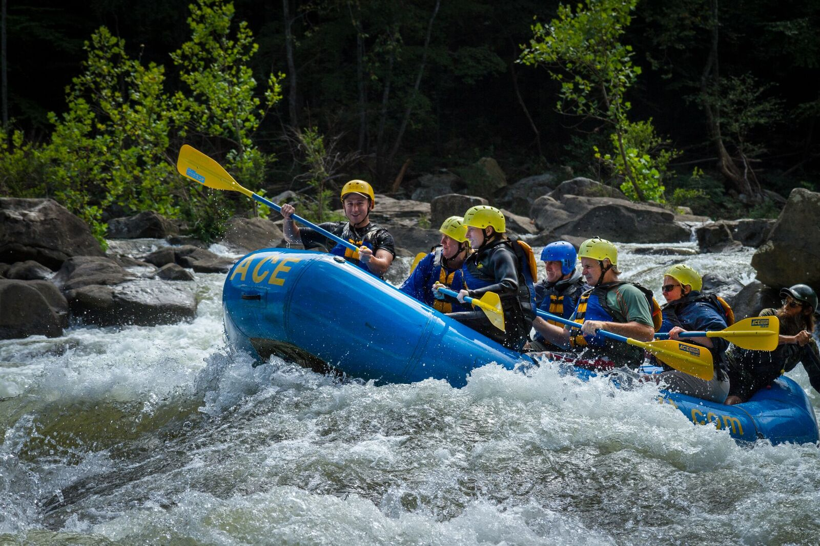 A group of 6 riding over a rapid on an ACE Adventure lower gauley rafting trip