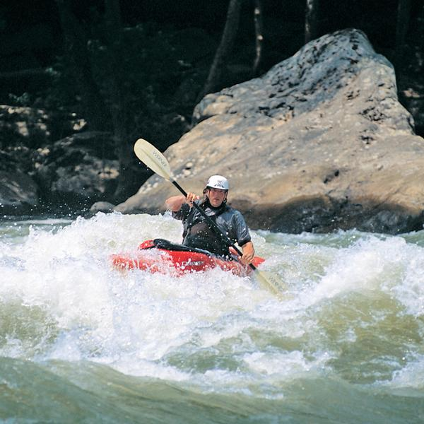 A kayaker practicing his paddling on a rapid during a kayak clinic