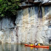 a kayaker in awe at cliff wall on a mountain lake tour