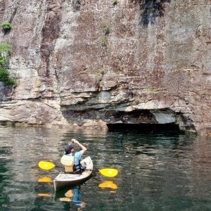 a kayaker checks out the cliff walls on a mountain lake tour