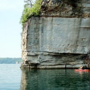 a kayaker takes in the spectacular cliff wall on summersville lake