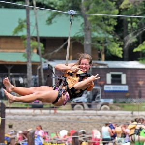 a young girl ziplines towards the waterpark lake