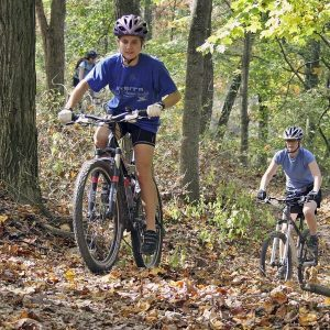 mountainbikers riding a trail in the fall