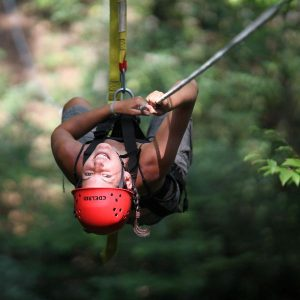 an upside down zipliner hanging out on the line on a canopy tour