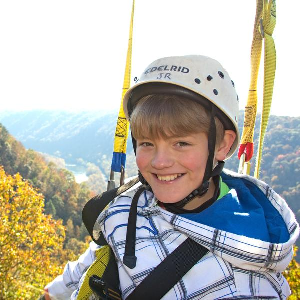 a young zipliner smiles as he zips across the best view on the canopy tour