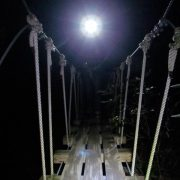 A zipliner crossing the first bridge on the canopy tour on a night zip