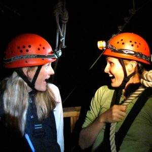 two female zipliners share a moment on a night zipline tour