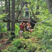 a couple race across the zip course side by side on a summer canopy tour