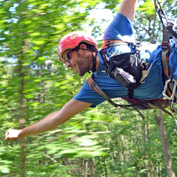 a zipline guide flies like superman through the trees