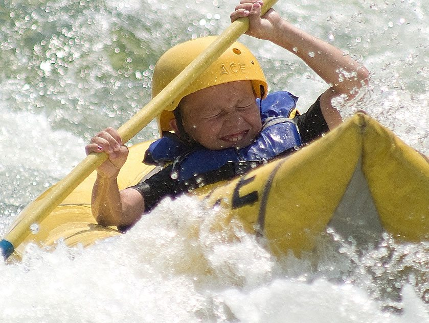 young boy goes through whitewater on the upper new