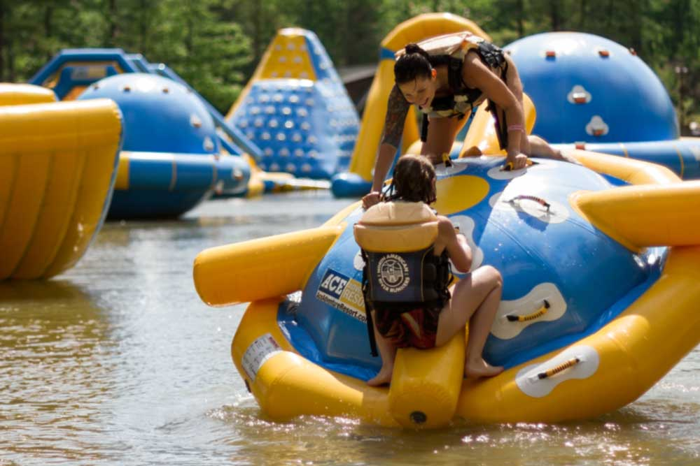 Friends playing on an inflatable at Wonderland Waterpark